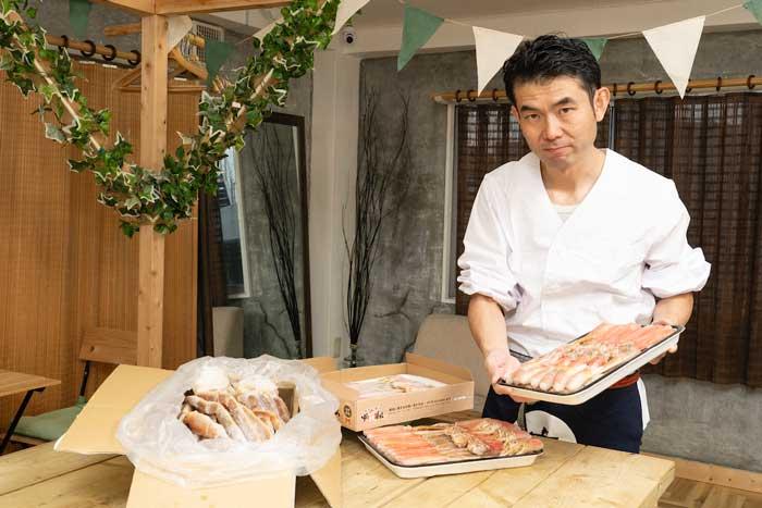 浅井さんがカニを持っている画像
