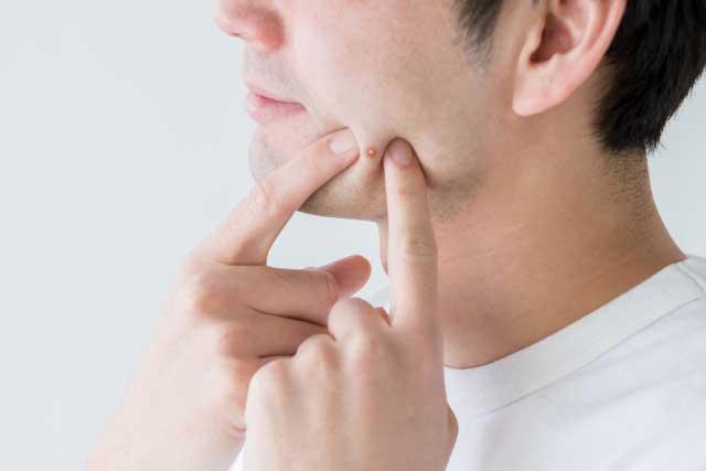 頬を指さす男性